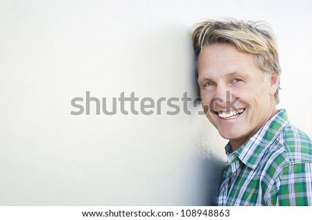 happy smiling mature man in forties leaning against a white wall. - stock photo