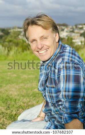 happy smiling mature man in forties sitting in a park and wearing a blue checked shirt. - stock photo
