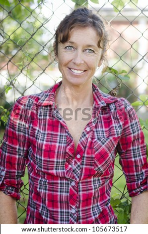 happy smiling mature woman in her forties wearing a red checked shirt. - stock photo