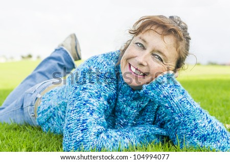 happy smiling mature woman laying on grass - stock photo