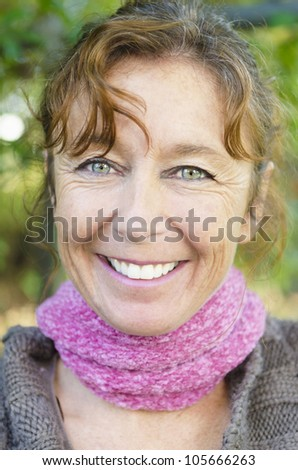 happy smiling mature woman with brown hair and green eyes wearing a pink scarf. - stock photo