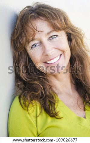 happy smiling mature woman with long auburn hair and freckles wearing a lime green jumper. - stock photo