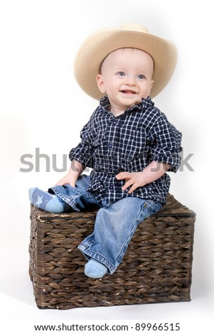 happy smiling 8-month old baby boy . Little cowboy sitting on the floor - stock photo