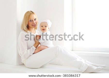 Happy smiling mother and baby at home in white room near window - stock photo