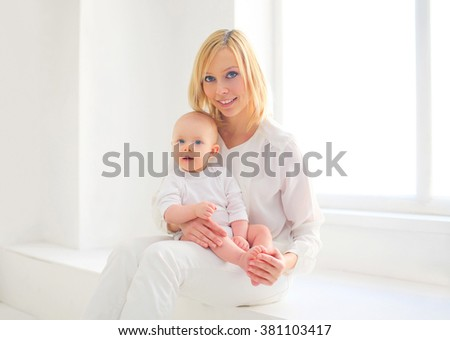 Happy smiling mother and baby home in white room near window - stock photo