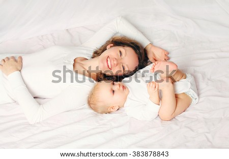 Happy smiling mother and baby lying on bed at home - stock photo