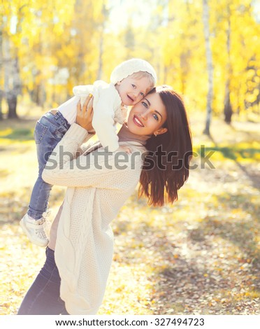 Happy smiling mother and child playing having fun in sunny autumn day - stock photo