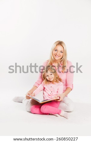 Happy smiling mother and child reading a book together - stock photo