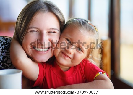Happy smiling mother and little daughter. Close-up family portrait. Shallow depth of field.  Selective focus on the model's faces. - stock photo