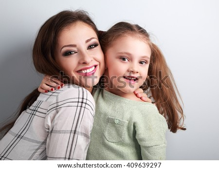 Happy smiling mother cuddling playful emotional fun daughter in studio on blue background. Closeup portrait - stock photo