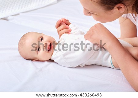 Happy smiling mother with baby in the bad. - stock photo
