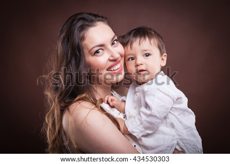 Happy smiling mother with her son in hands on brown background in studio photo - stock photo