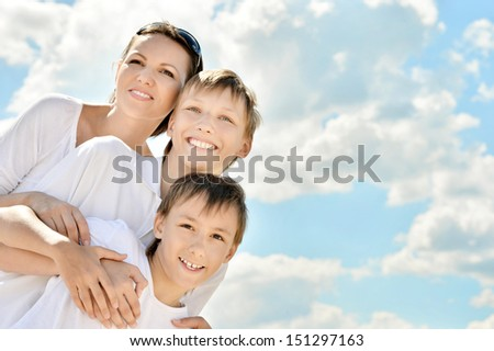 Happy smiling mother with her sons on sky background - stock photo