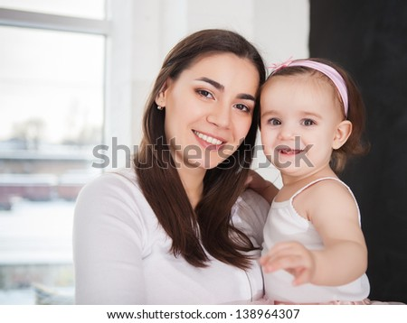 Happy smiling mother with one year baby girl indoor - stock photo