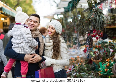 Happy smiling parents with little daughter at counter with Poinsettia. Shallow focus - stock photo