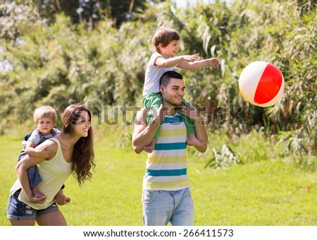 Happy smiling parents with little daughters playing with ball outdoor - stock photo