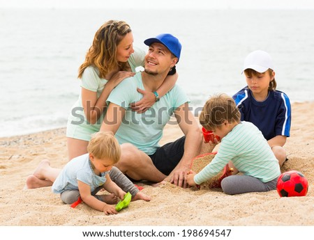 Happy smiling parents with three children having fun in vacation on seashore - stock photo