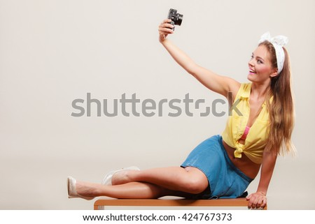 Happy smiling pretty pin up girl wearing hairband bow, skirt and high heels taking photo picture with camera. Attractive gorgeous young retro woman photographing. - stock photo