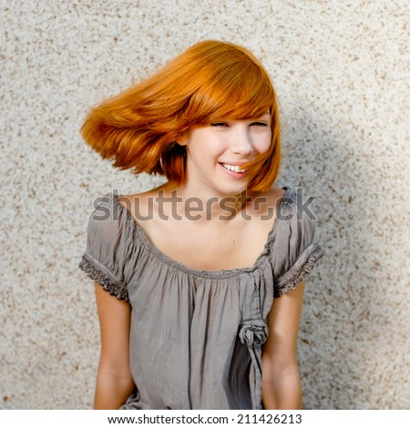 happy smiling redhead pretty girl having fun enjoying wind blow & looking at camera on copy space gray wall background, closeup portrait - stock photo