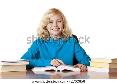 Happy smiling school girl sitting at desk reading books. Isolated on white background. - stock photo