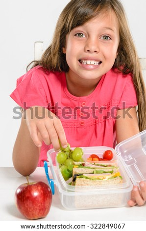 Happy smiling school girl with healthy lunchbox filled with fresh fruit and sandwich - stock photo
