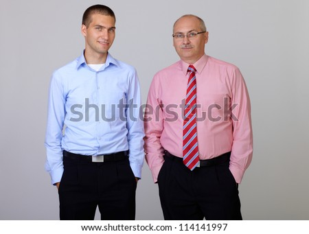 Happy smiling senior and junior businessman standing with hands in pockets, isolated on grey - stock photo