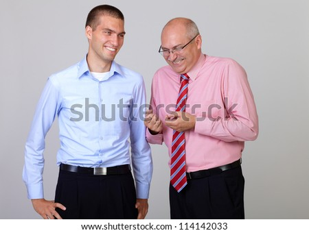 Happy smiling senior businessman with his junior businessman colleague, isolated on grey - stock photo