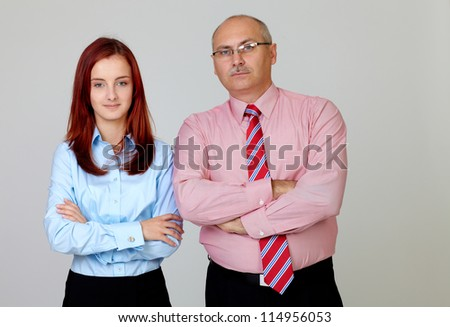 Happy smiling senior businessman with young attractive businesswoman in shirts with hands folded, isolated on grey - stock photo