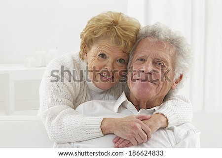 Happy smiling senior couple embracing together at home  looking to camera - stock photo