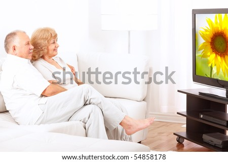 Happy smiling senior couple watching TV at home - stock photo