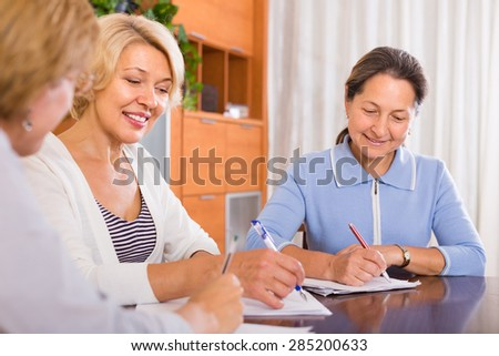 Happy smiling senior ladies signing documents at notary. Focus on brunette - stock photo