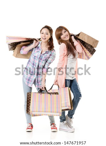 Happy smiling shopping girls of Asian holding bags, full length portrait isolated on white background. - stock photo