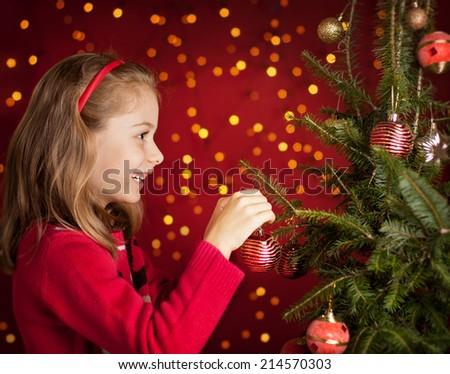 Happy smiling six years old blond caucasian child girl decorating christmas tree on dark red background with lights - stock photo