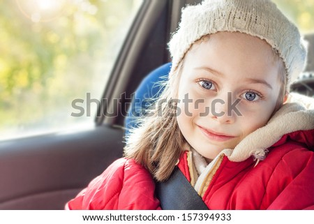 Happy smiling small five years old caucasian girl in warm clothes traveling in a car seat - close up autumn portrait - careless childhood - stock photo