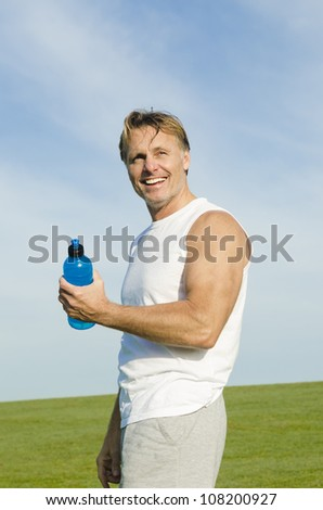 happy smiling sportsman fooling around with his water bottle. - stock photo