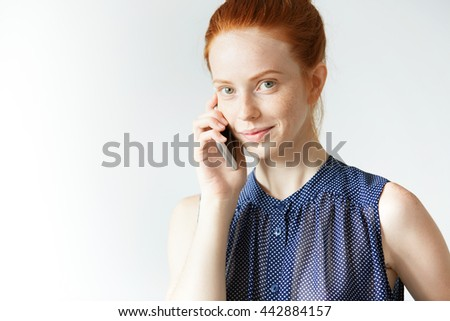 Happy smiling student girl looking at the camera with cheerful expression, calling her parents, telling that she successfully passed final exams, against white copy space wall for your advertisement - stock photo