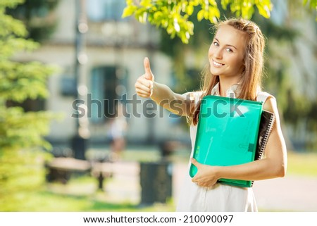 Happy smiling student woman is standing in the university campus and showing thumb up for a successful year in college.  - stock photo