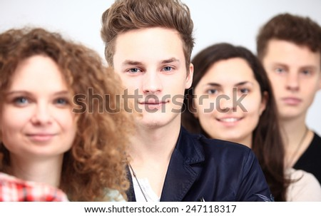 Happy Smiling Students Standing In Row. Young people standing in a row while beautiful young man standing in front of them and smiling - stock photo