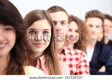 Happy Smiling Students Standing In Row. Young people standing in a row while beautiful young woman standing in front of them and smiling - stock photo