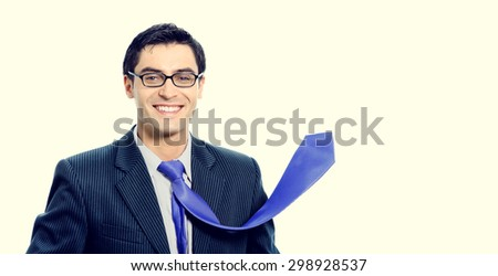 happy smiling successful young businessman with raised up blue tie. Growing business or profit concept. - stock photo