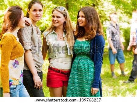 Happy smiling teenage girlfriends in summer park - stock photo