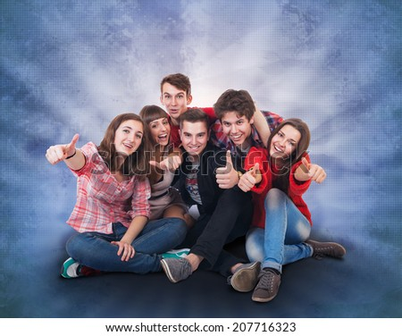 Happy smiling teenagers group on bright green background - stock photo