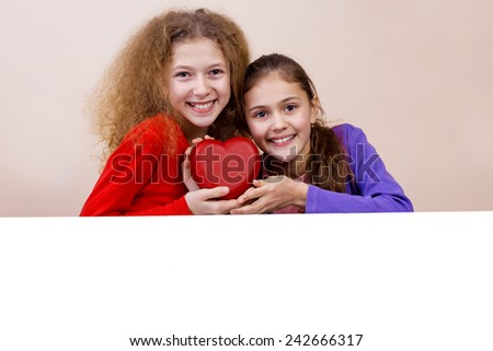 Happy, smiling  two little girl holding Red heart and showing white blank placard, board,poster.Concept Love,Care,Health.Facial expression. - stock photo
