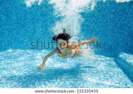 Happy smiling underwater child jumps to swimming pool, beautiful little girl swims and having fun. Kids sport on family summer vacation. Active healthy holiday - stock photo