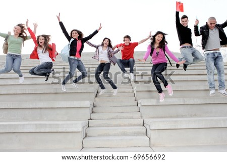 HAPPY,SMILING UNIVERSITY KIDS JUMPING ON CAMPUS - stock photo