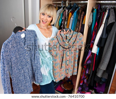 happy smiling woman choosing clothes in front of full closet - stock photo