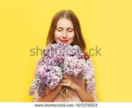 Happy smiling woman enjoying smell of bouquet lilac flowers over yellow background - stock photo