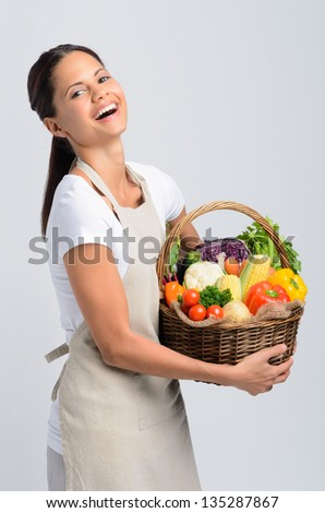 Happy smiling woman holding a basket of raw organic produce vegetables wearing an apron, healthy eating living concept - stock photo