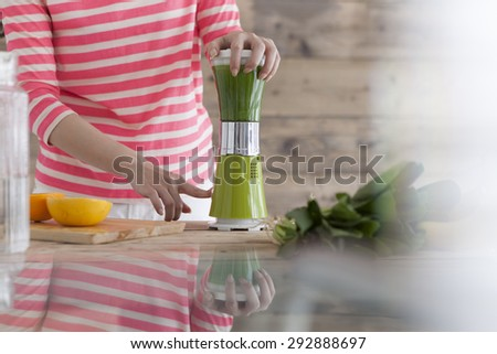 Happy smiling woman in kitchen preparing fresh vegetables cocktail - stock photo