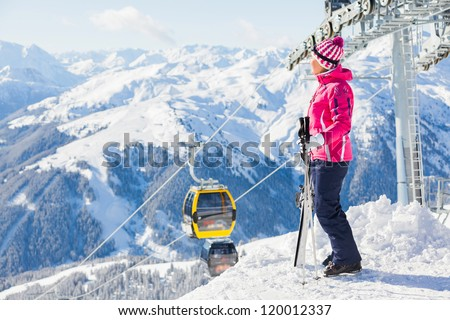 Happy smiling woman in ski goggles against a ski-lift and wonderful winter mountains backgroundagainst wonderful winter mountains background and , Zellertal, Austria - stock photo